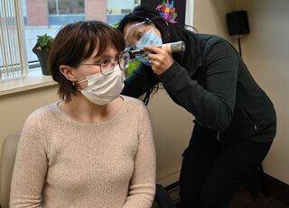 Audiologist and patient wearing a face mask